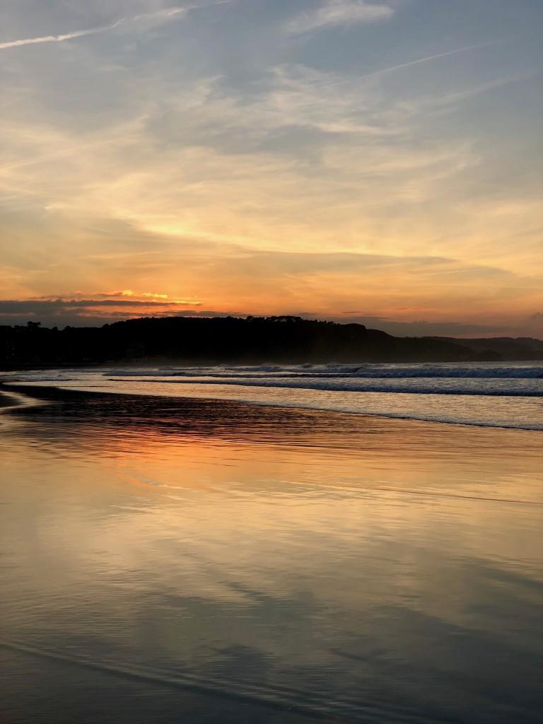 The sun sets over the beach