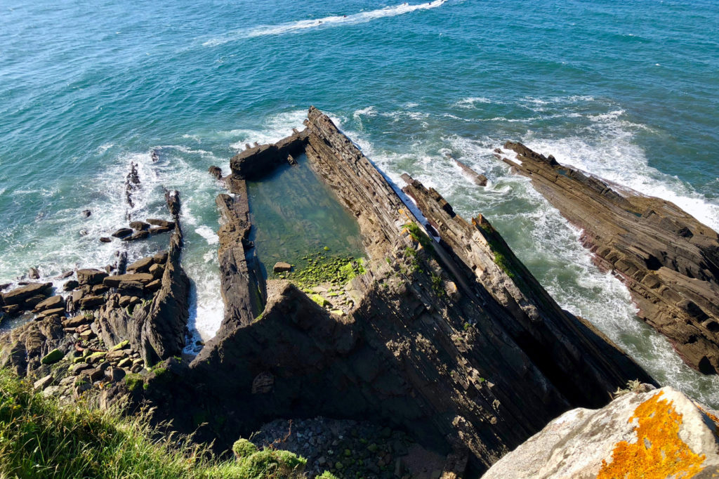 A natural pool at the base of the cliffs