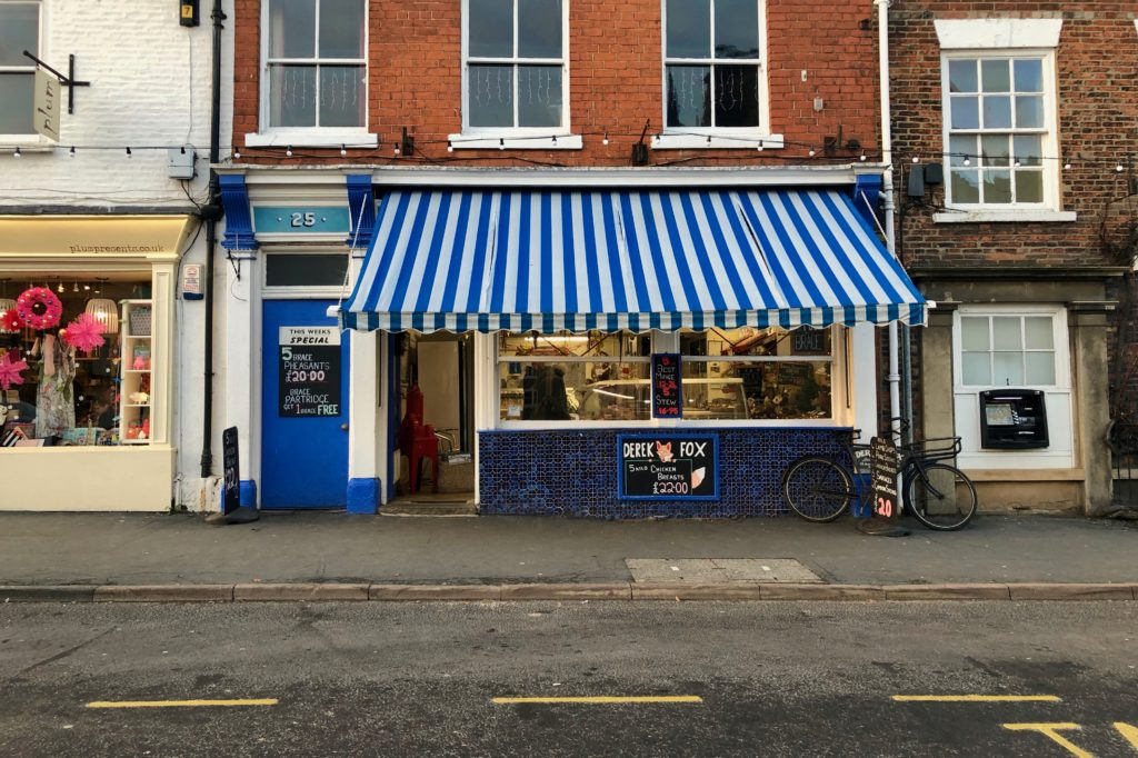 Butchers hiding under their awning