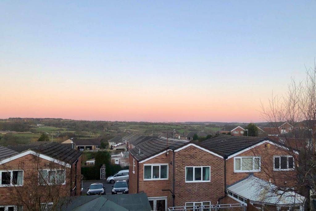 An orange and blue sunrise behind a hill, with houses in the foreground.