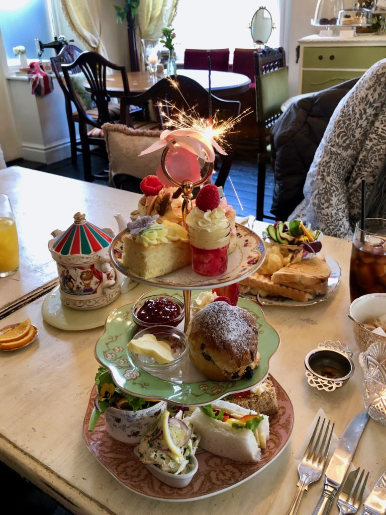 An afternoon tea topped with a lit sparkler.