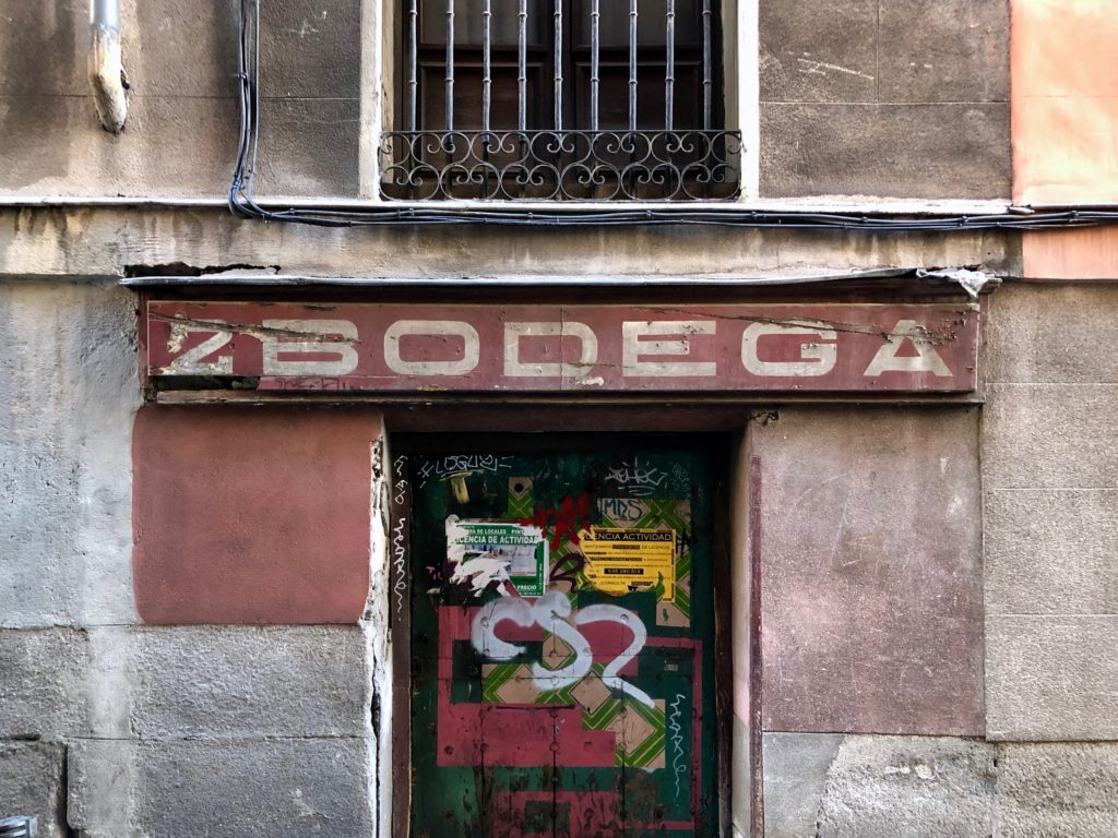 "A fading facade reads ""Bodega"" in old handwritten letters."