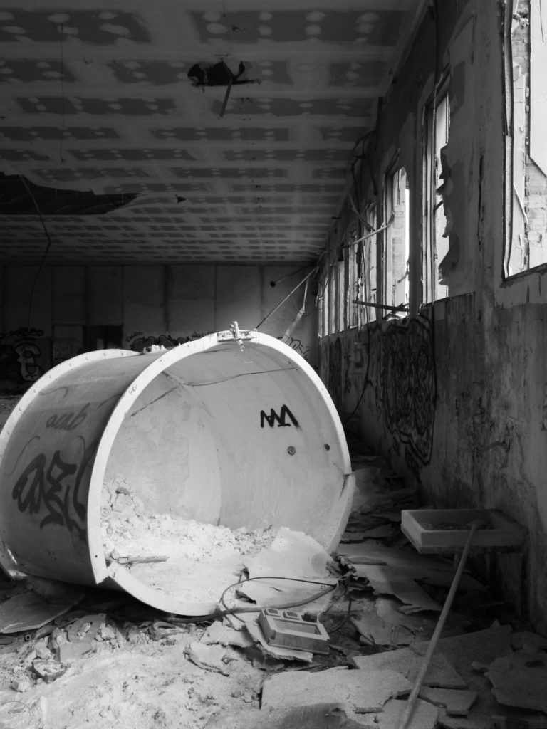 A broken container full of white powder sits in an abandoned factory.