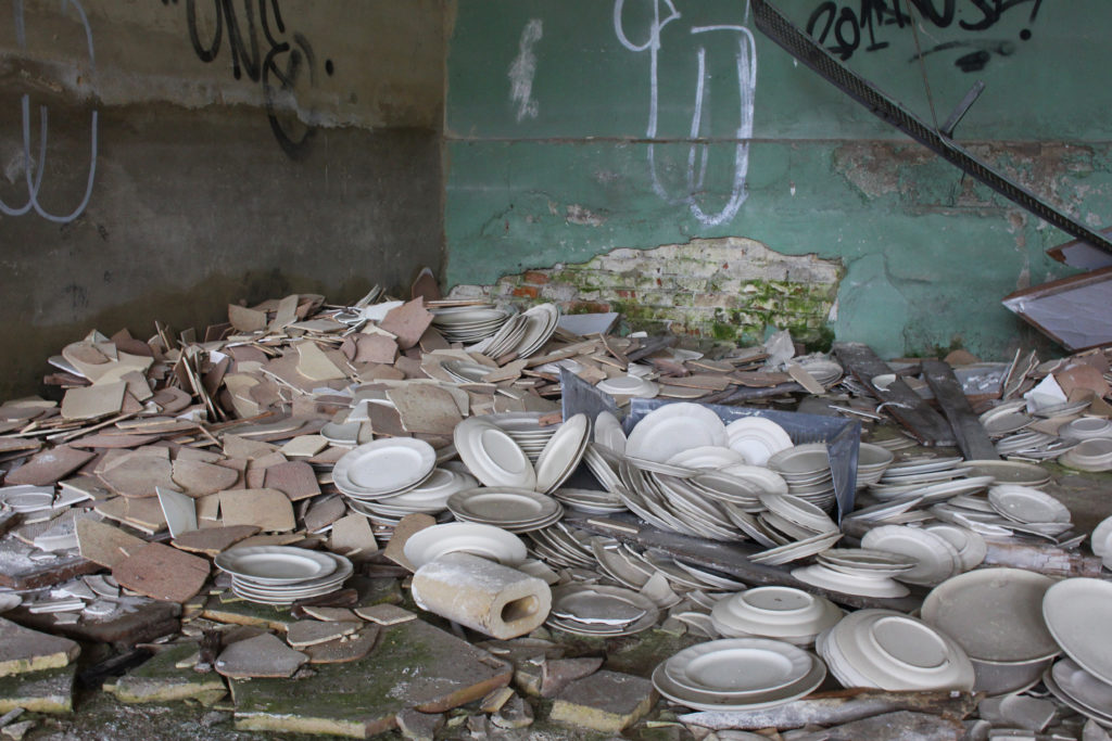 A pile of unfinished ceramics sit in the corner of an abandoned factory.