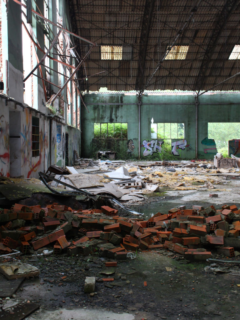 An abandoned factory warehouse, with bricks in the foreground and decaying walls covered in graffiti.