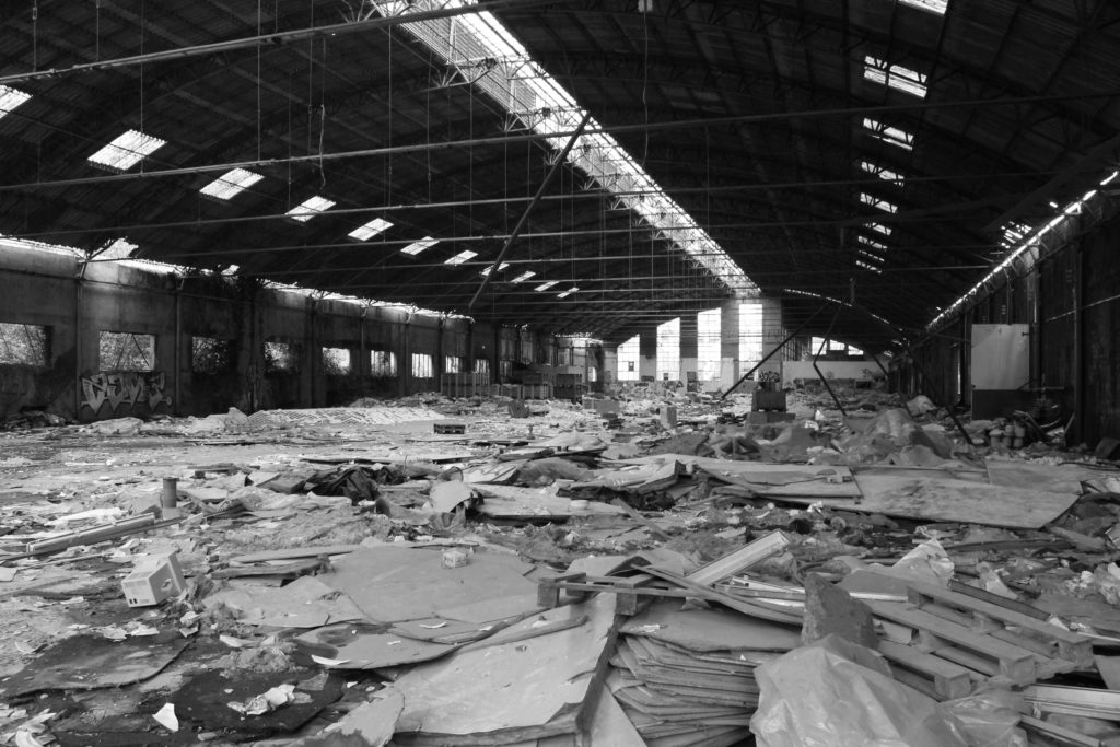 An abandoned factory warehouse littered with debris.