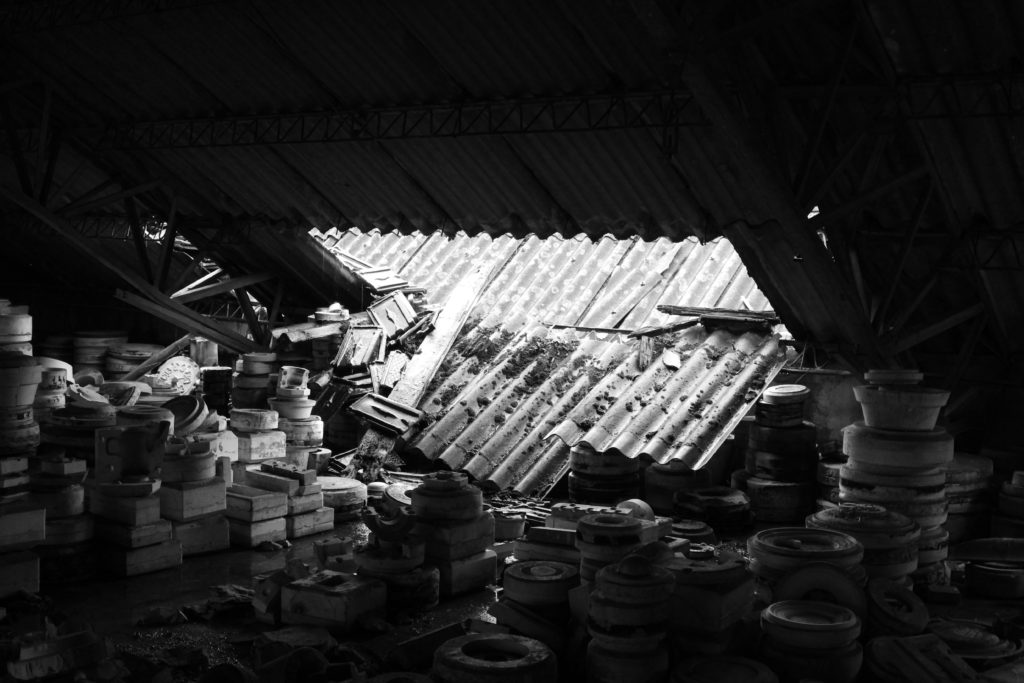 A roofing panel collapses, allowing light in to reveal an abandoned factory room full of ceramic moulds.