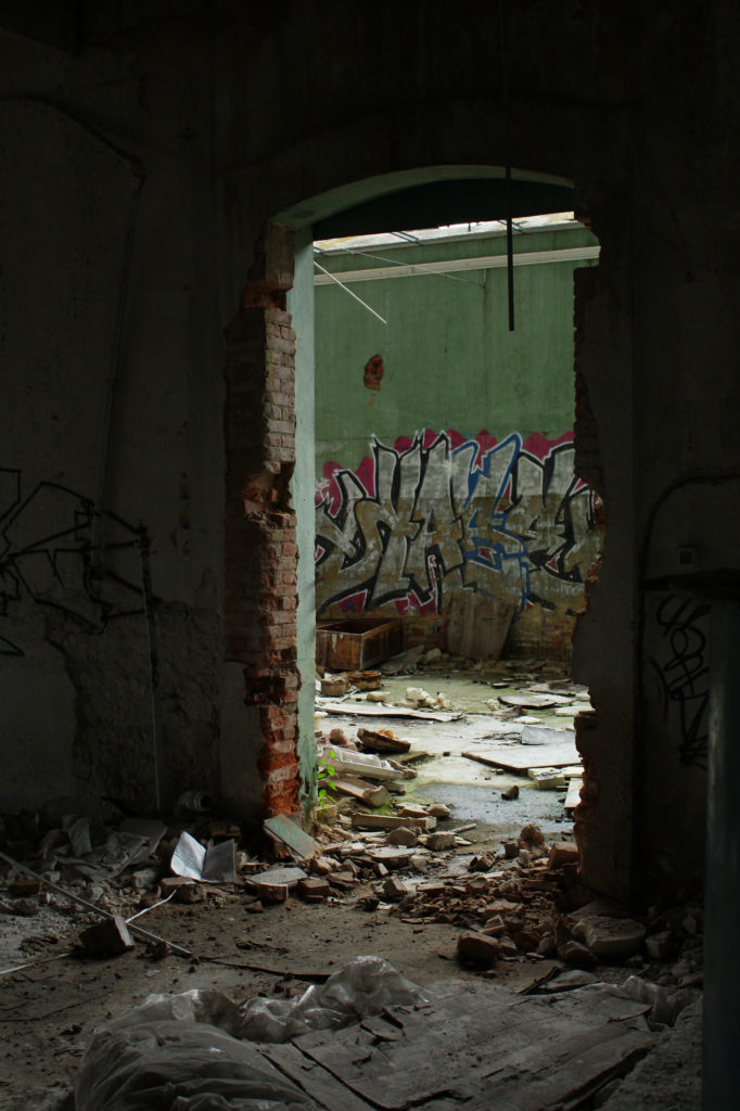 A doorway through an abandoned factory leading to a room full of graffiti.