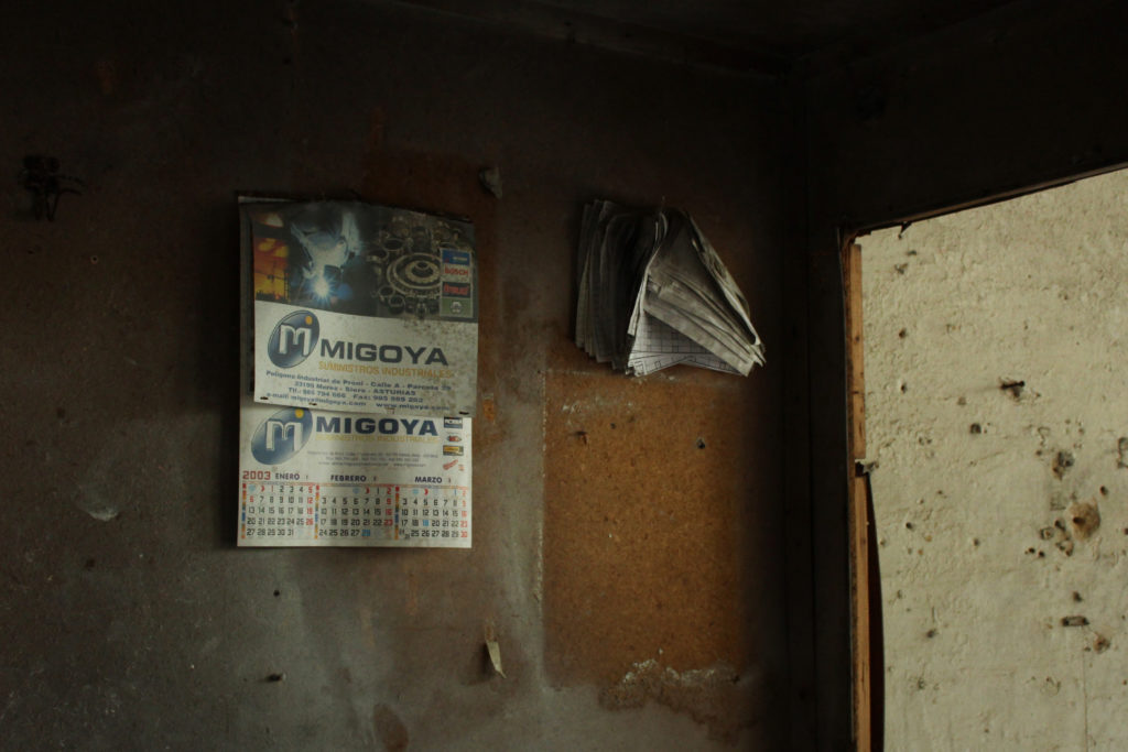 A wall shows a decaying calendar dated 2003.