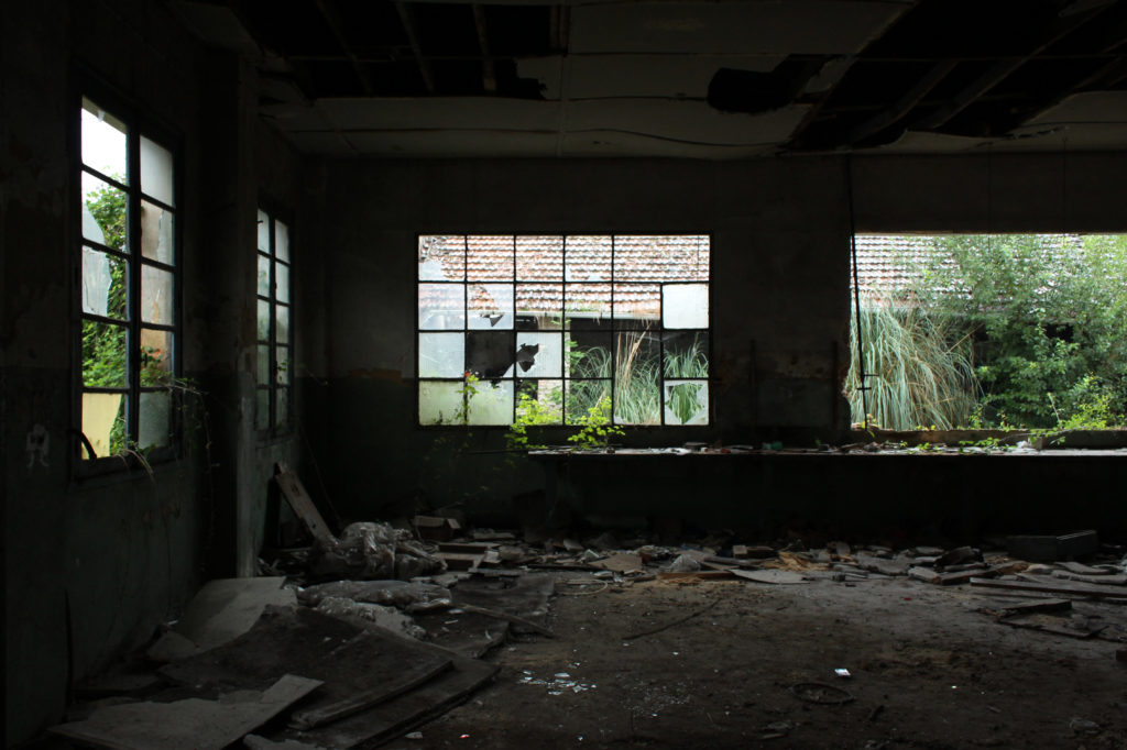 An abandoned workshop with shattered windows.