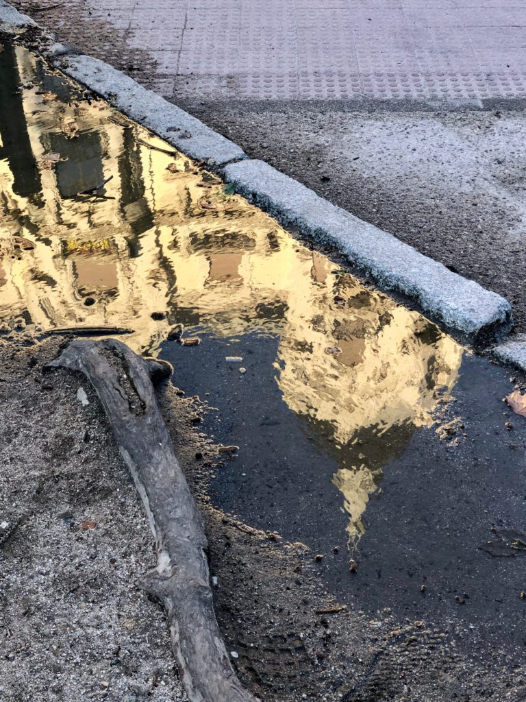 A baroque building lit by the orange sun is reflected in a puddle on a grey pavement.