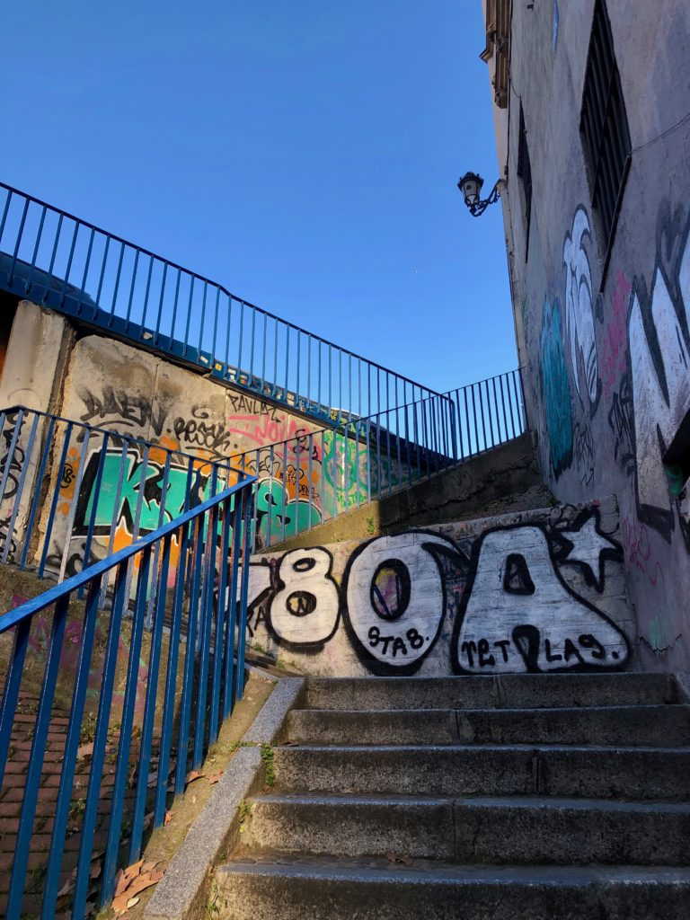 A blue sky above a graffiti-covered stairwell lit by the setting sun.