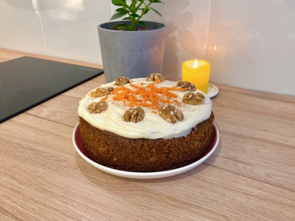 A carrot cake topped with cream cheese frosting, grated carrots, cinnamon, and walnuts.