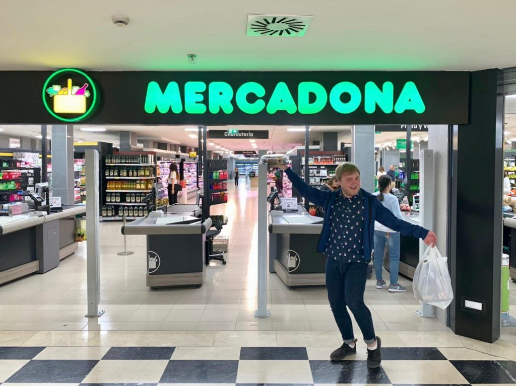 Me stood outside Mercadona, holding a cake in one hand and a bag full of shopping in the other.