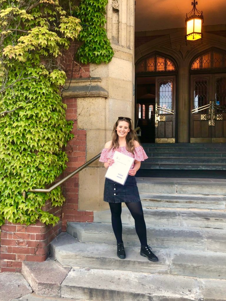My sister holds her dissertation outside a building at Sheffield University.