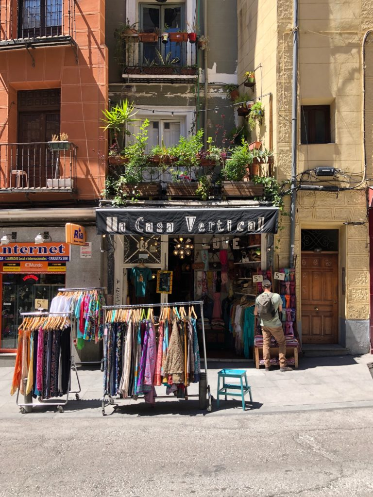 Clothes sit on a rack on the side of a sunny Madrid street.