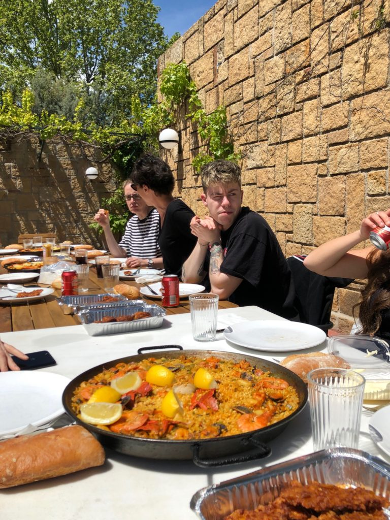 Paella, beers, and other food spread out on a table.