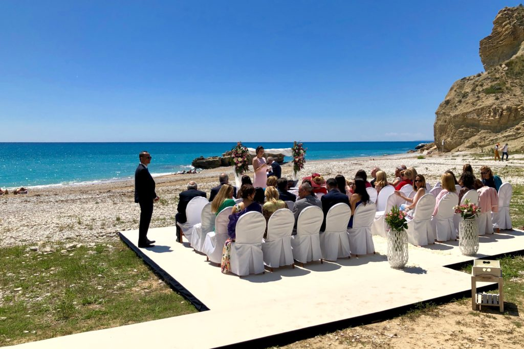The wedding party seated on the beach platform.