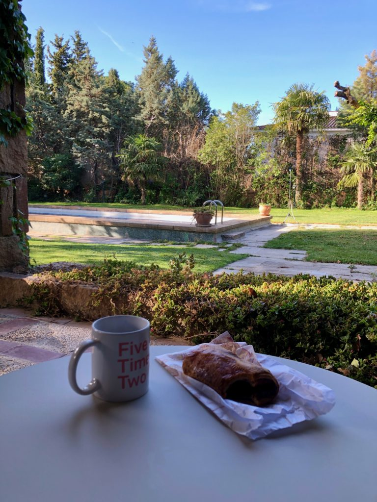 A breakfast pastry and coffee on a table on a porch. Garden and pool in the background.