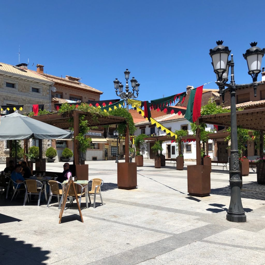 A plaza in Manzanares, with celebration bunting and traditional lamps.