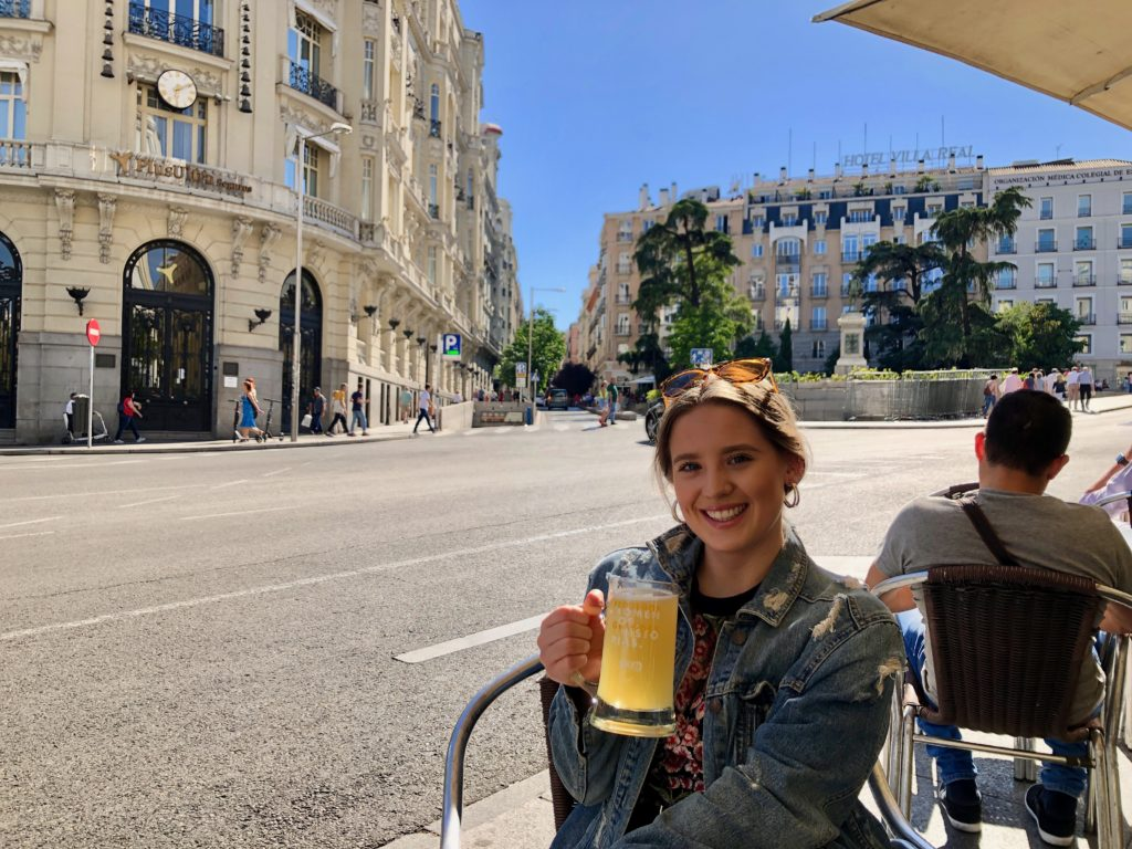 Ellie with a drink sat in a plaza in Madrid.