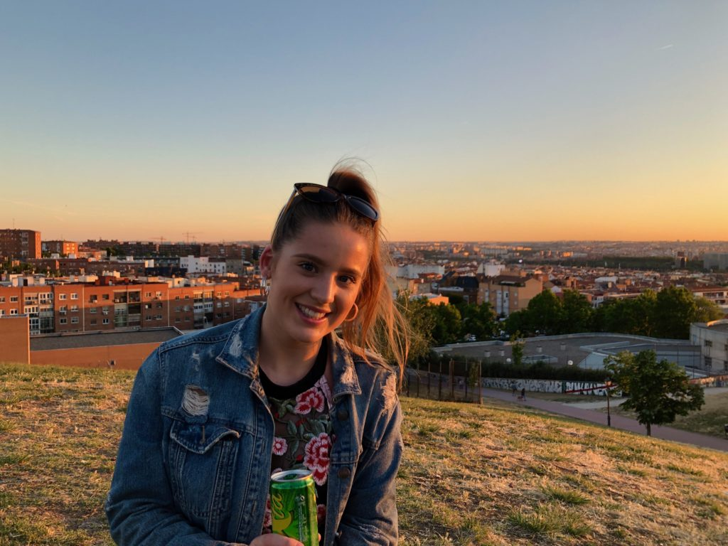 Ellie in Vallecas, Madrid, with the city skyline in the background as the sun sets.