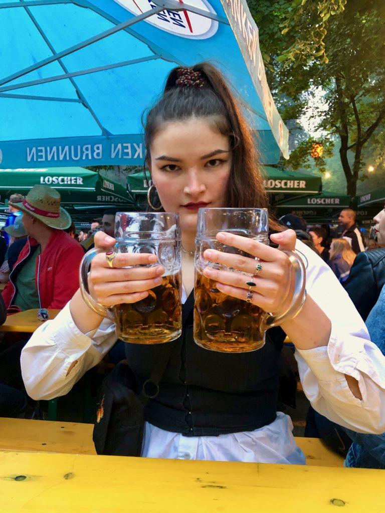 Evie holds two jars of beer at the beer festival.