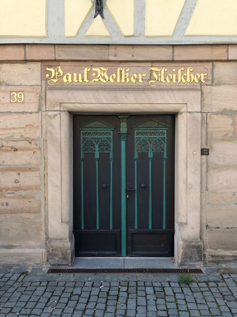 "A gold sign reading ""Paul Belker Fleischer"" stands over a door."