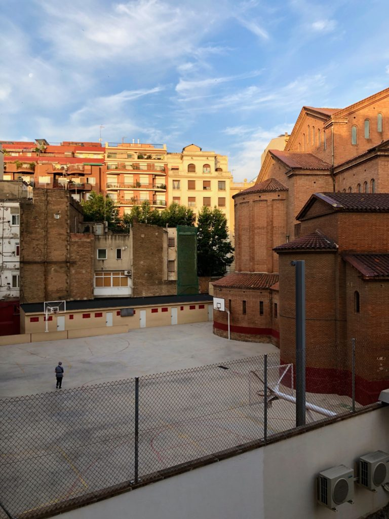 The view from our hotel room in Barcelona. The sun rises, illuminating buildings in a warm glow. A lone man walks through a courtyard below.