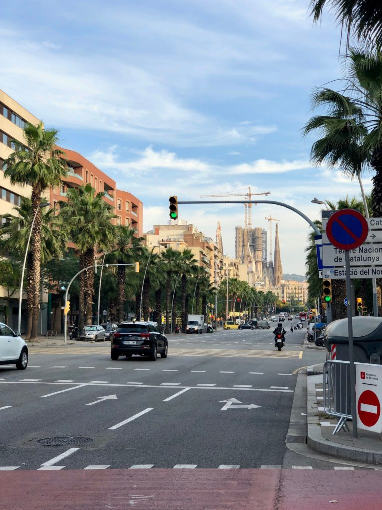 The Sagrada Familia in its unfinished state, with a Barcelona boulevard in the foreground.