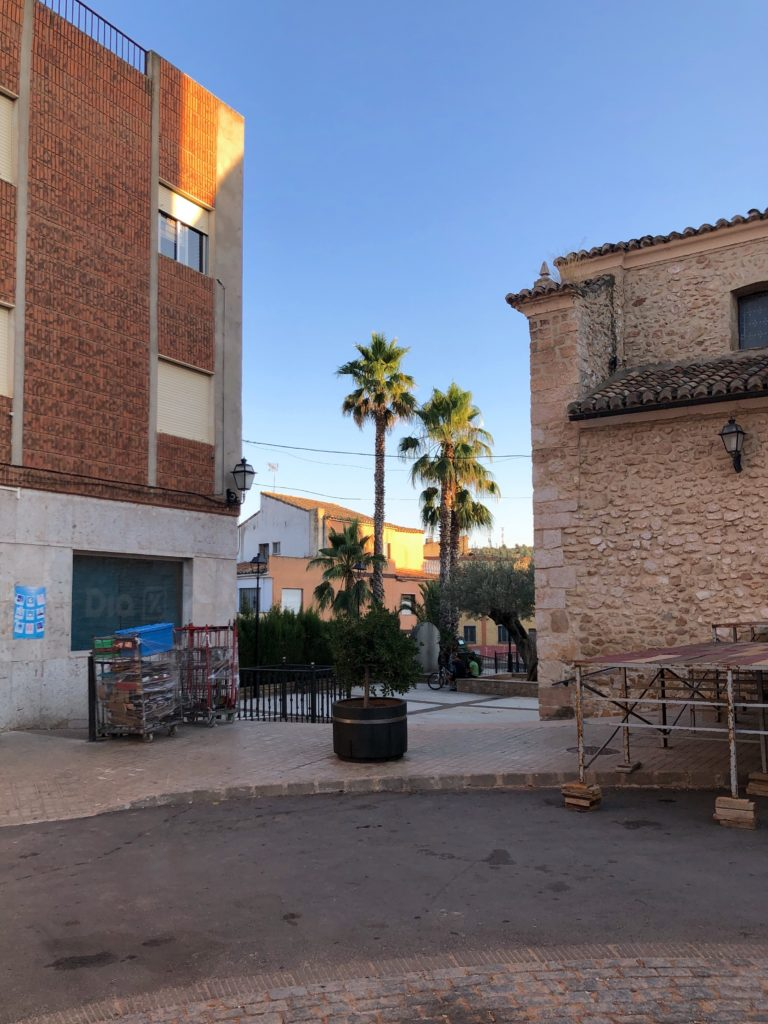 The centre of Caudete de las Fuentes, including a shop some palm trees, and the corner of a church.