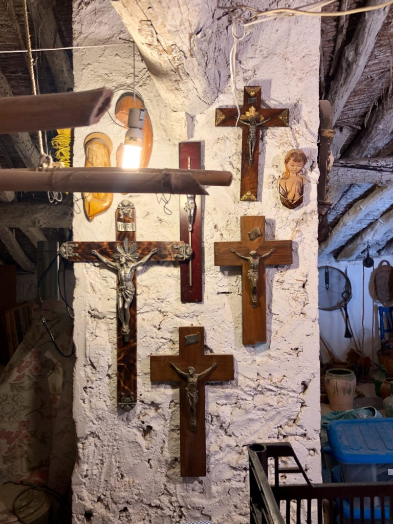 An arrangement of Christian crosses on the column of an old loft.