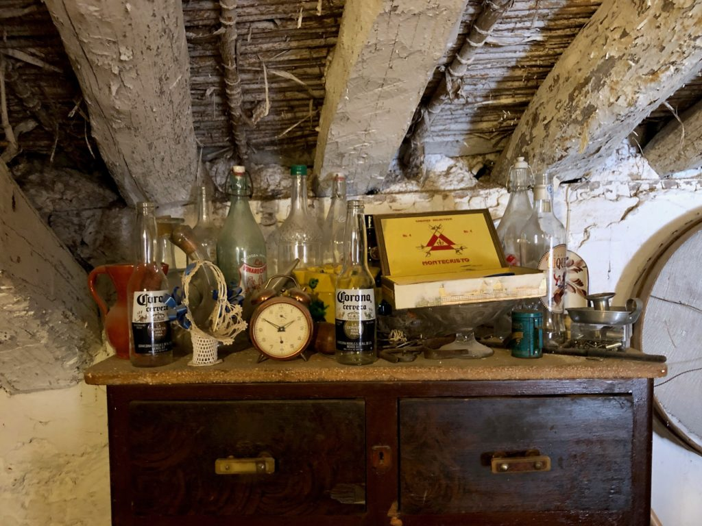 An old chest topped with glass knickknacks and hidden under the rafters of an old roof.