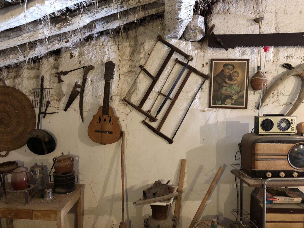A selection of old tools and objects hung off the wall in an old loft.