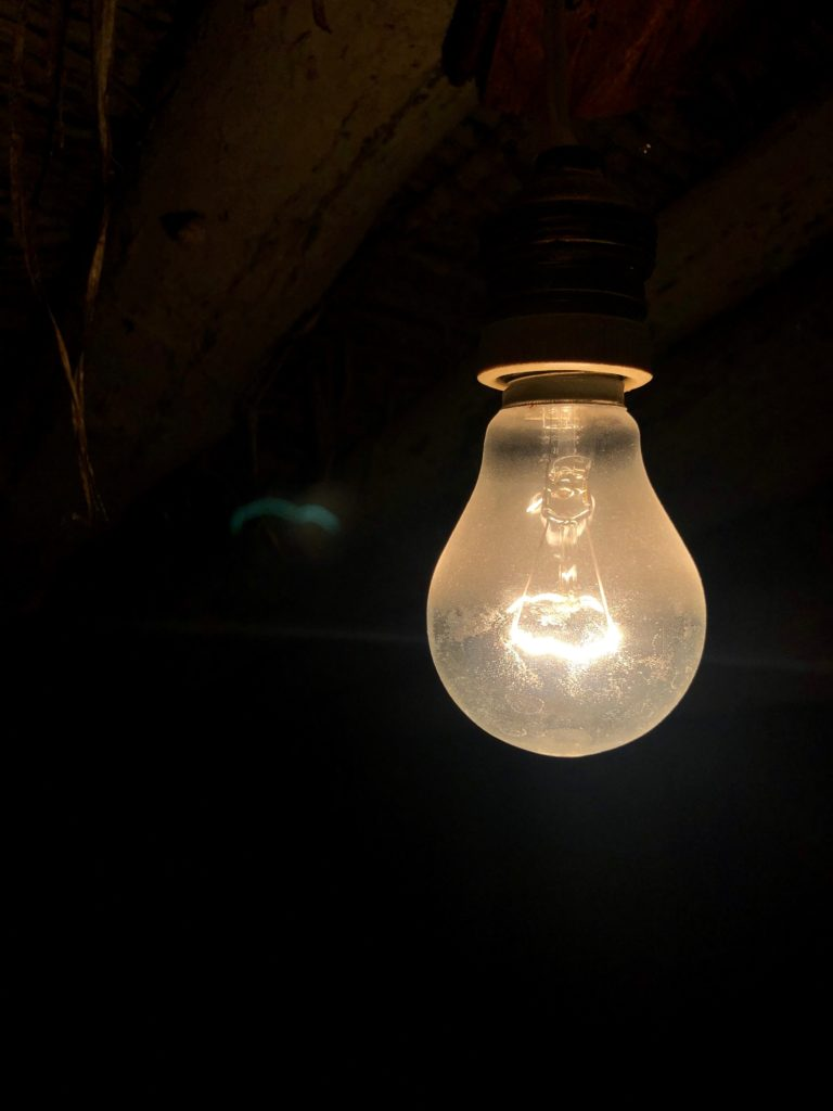 An old incandescent lightbulb burns in the loft of an old house.