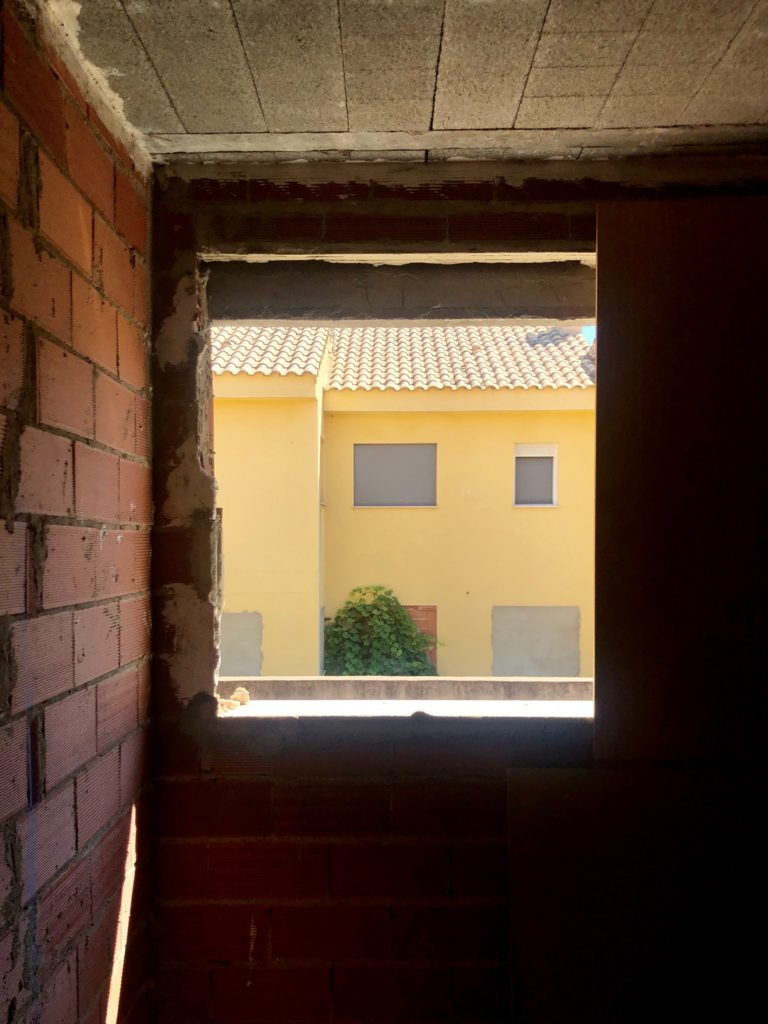 An abandoned house can be seen through the missing window of another abandoned house.
