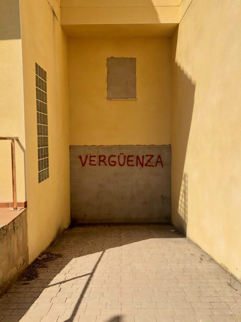 "The Spanish word ""vergüenza"", meaning shame, is graffitied onto the blocked-up entrance to the subterranean garage of an abandoned house."