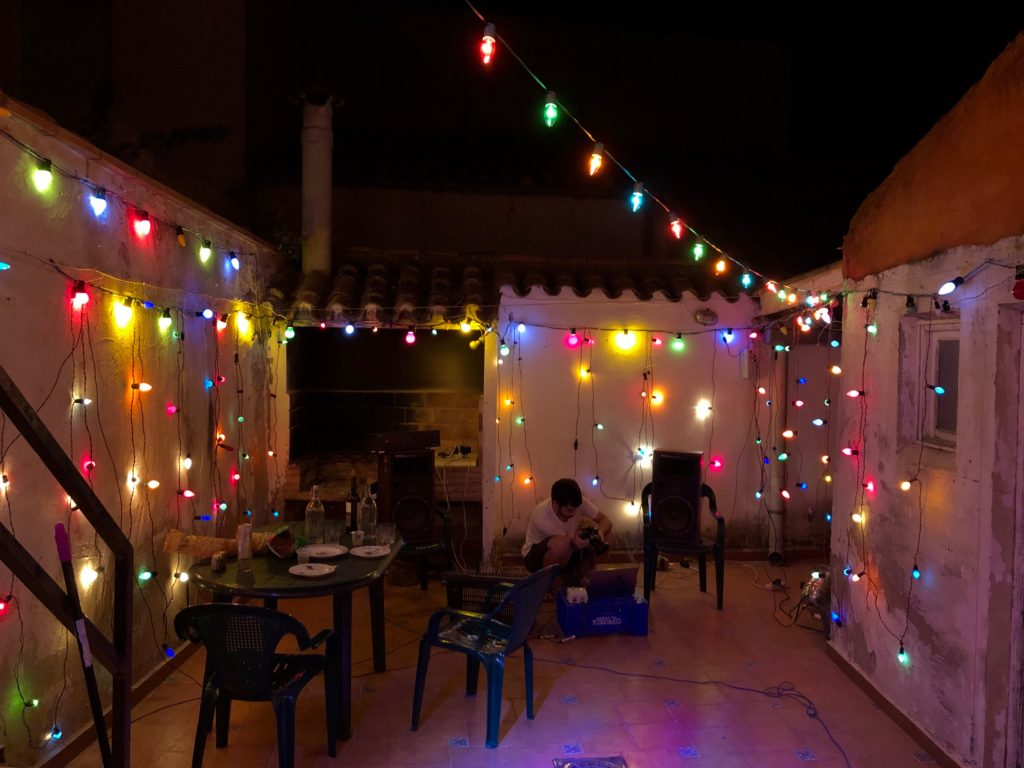 A patio at night illuminated by a web of multicoloured string lights which decorate the walls.