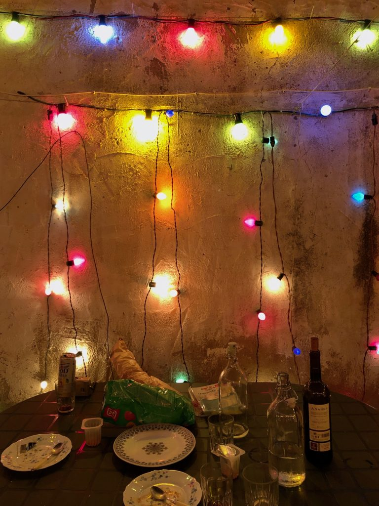 A web of lights on a wall sits behind a table littered with bottles and leftover food.