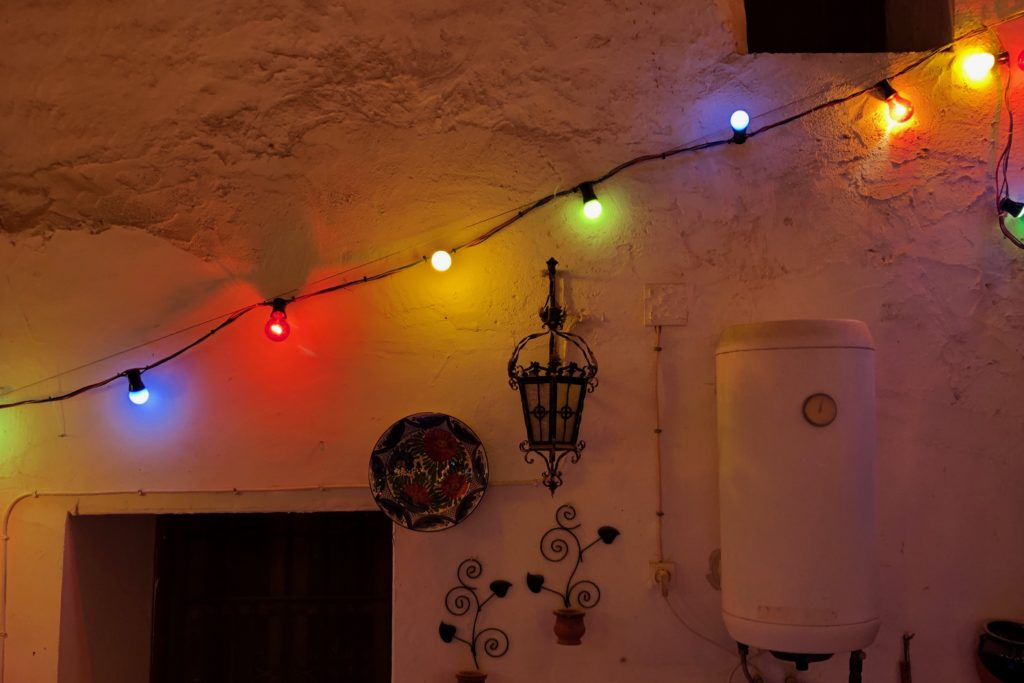 A string of red, green, yellow, and blue lights runs diagonally up a wall.