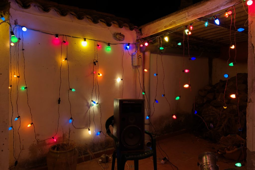 A speaker on a chair, with walls full of fairy lights in the background.