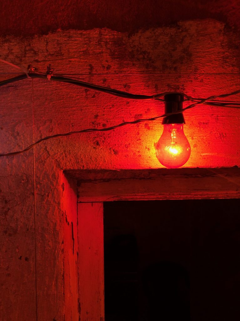 A red lightbulb against an old plaster wall and above an open doorway.