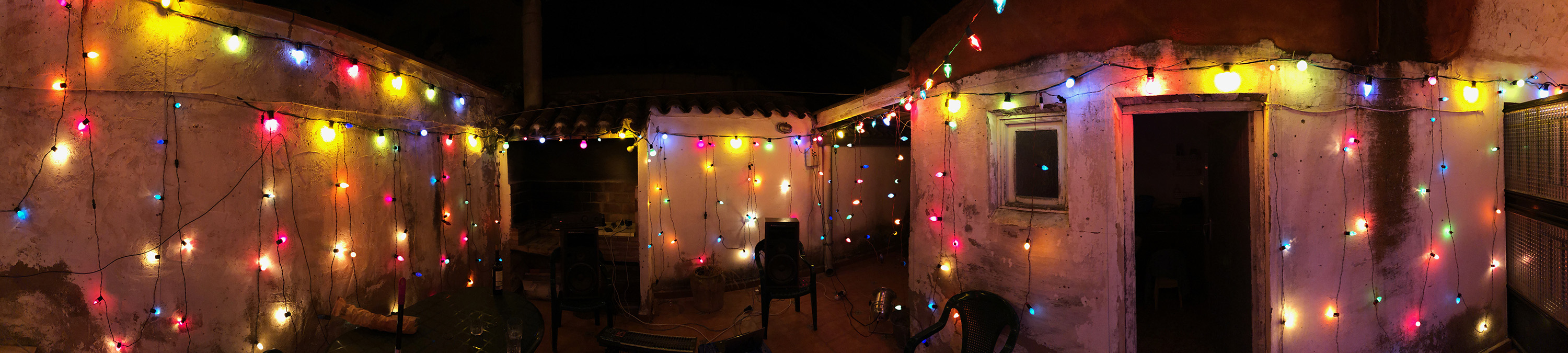 A panoramic shot of the patio decorated with lights.