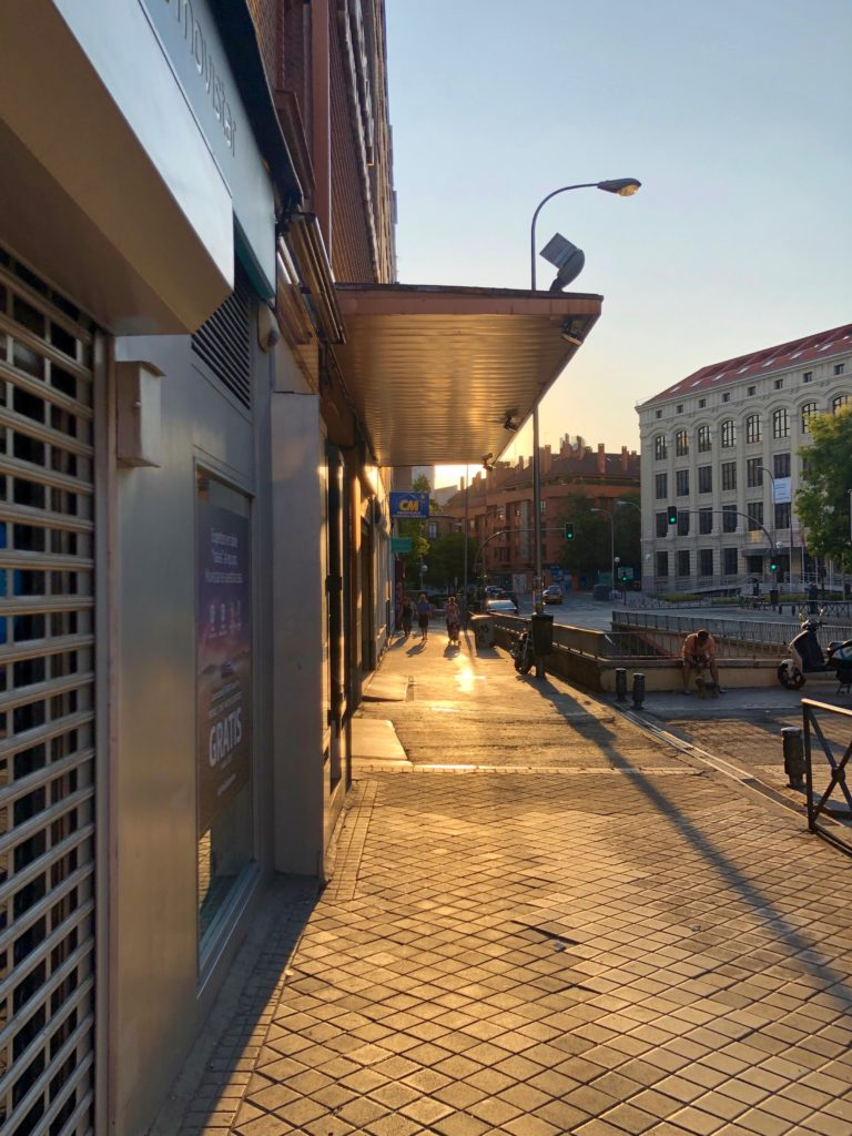 A low sun casts long shadows and illuminates the street in a warm glow.