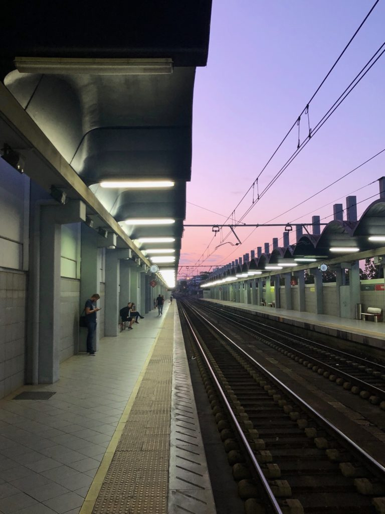 A pink, purple, and orange sunrise over the train lines of a station.