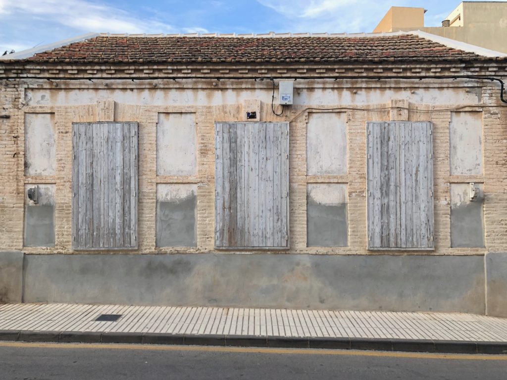 Three faded white shutters on a sun-bleached house.