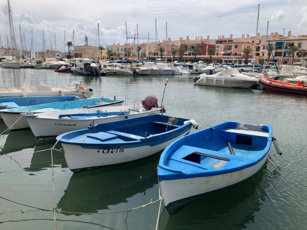 A row of blue boats in a harbour.