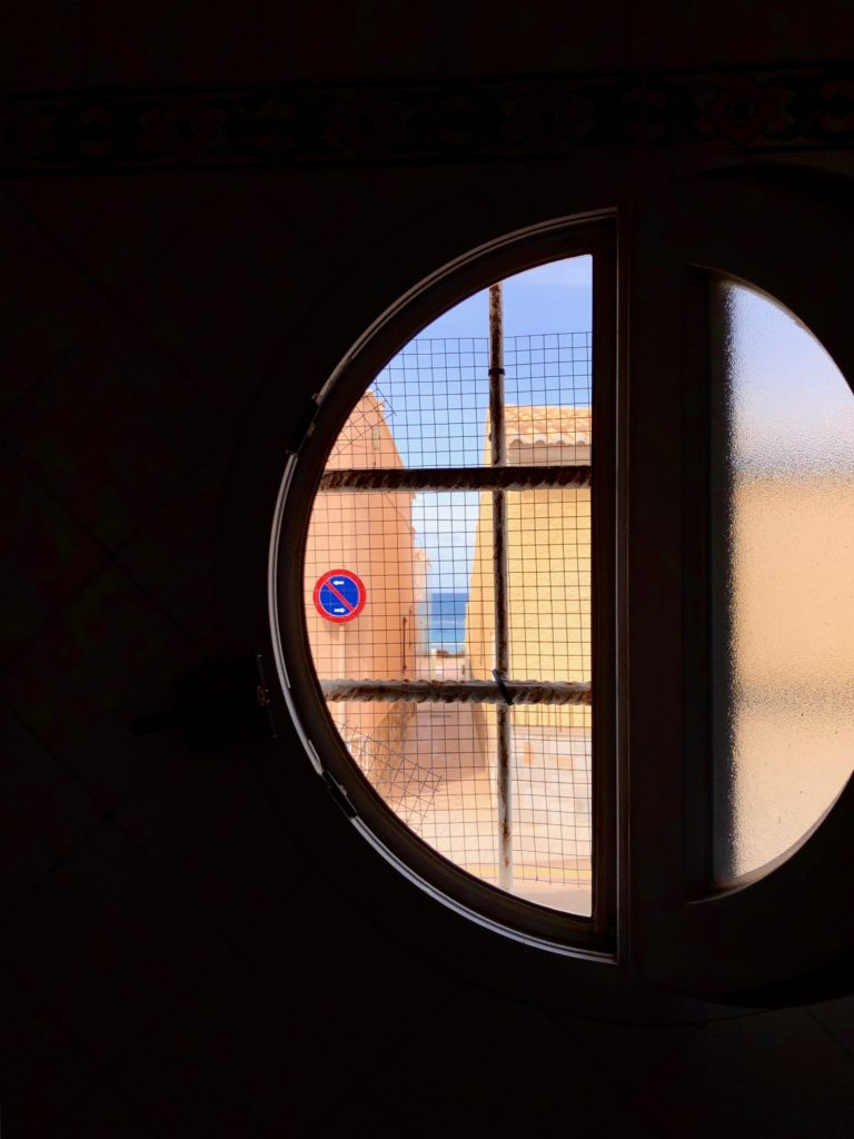 The sea is seen between two houses, which is all seen through a portal window.