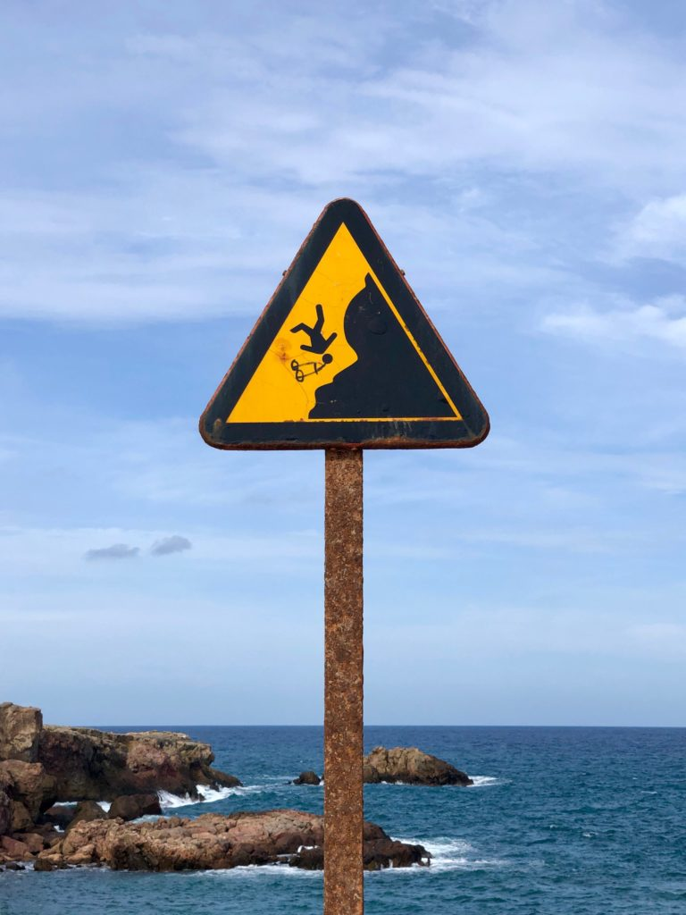 A sign warning of the risk of falling off a cliff.