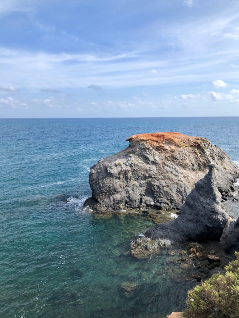 A colourful rock juts out into the sea.